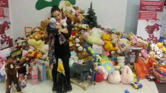 A girl holding fur toy next to pile of toys