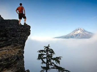 Man standing on rock edge looking at mountain top